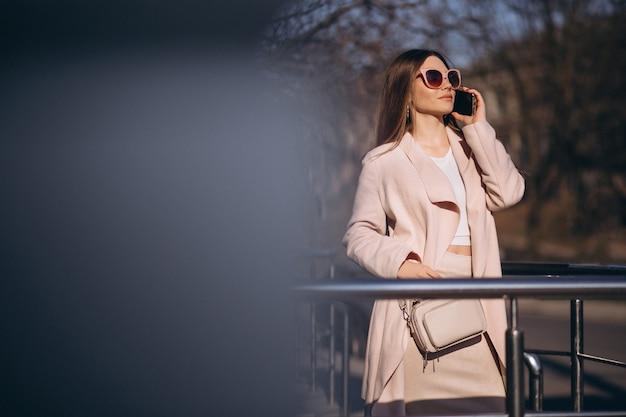Mulher de casaco andando na rua e falando ao telefone
