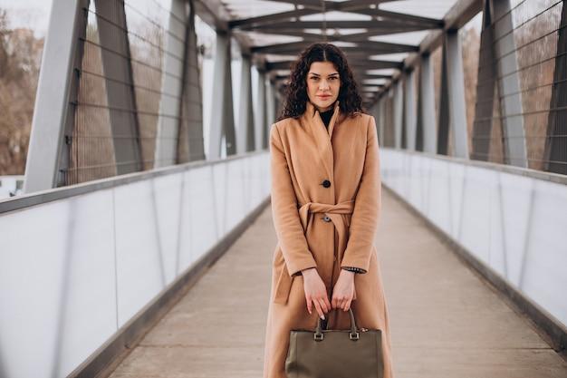 Mulher de casaco bege caminhando pela cidade