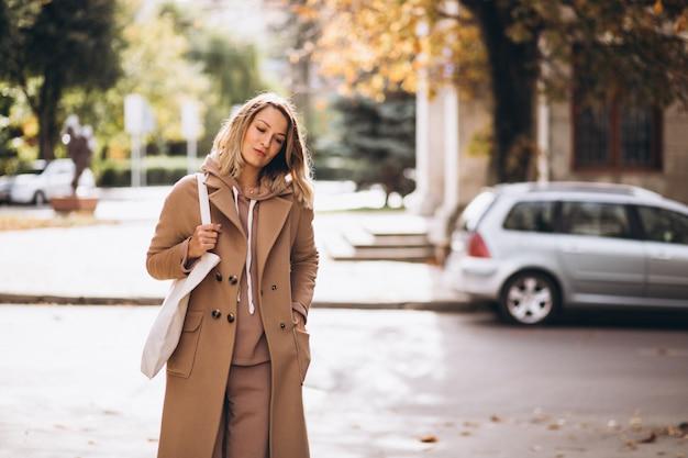 Mulher de casaco bege com sacola de compras na rua