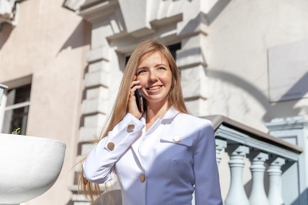 Mulher de casaco branco falando no telefone perto da escada vintage