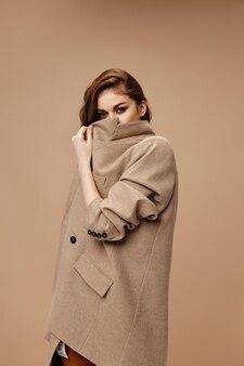 Mulher de casaco cobre o rosto com gola e modelo de fundo bege