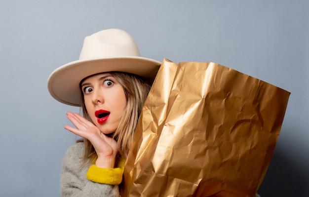 Mulher de casaco com sacola de compras