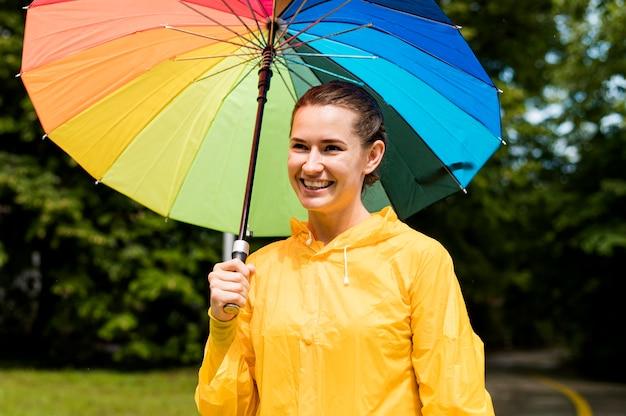 Mulher de casaco de chuva sorrindo enquanto segura um guarda-chuva
