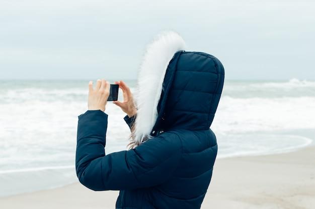 Mulher de casaco de inverno com capuz, usando um telefone celular na praia