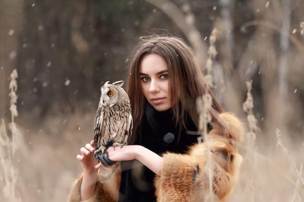 Mulher de casaco de pele com coruja na mão pela primeira neve do outono.