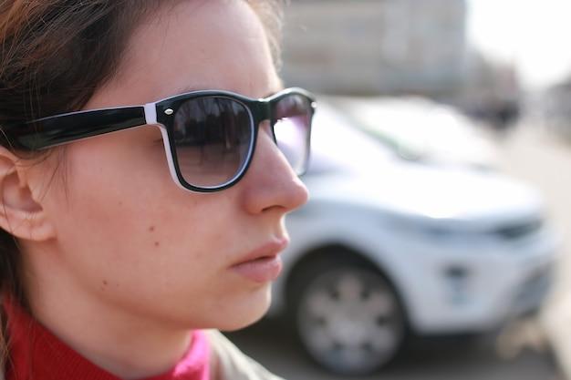 Mulher de casaco e óculos de sol de rua