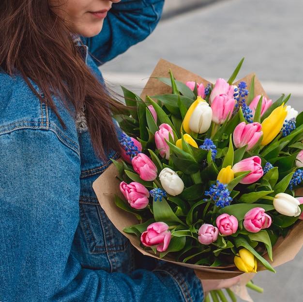 Mulher de casaco jeans com um buquê de tulipas coloridas.