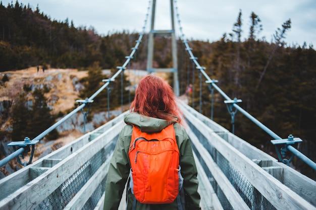 Mulher de casaco laranja e jeans azul em pé na ponte durante o dia