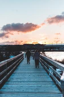 Mulher de casaco preto e jeans azul andando na doca de madeira durante o pôr do sol