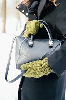 Mulher de casaco preto e luvas verdes detém uma bolsa close-up