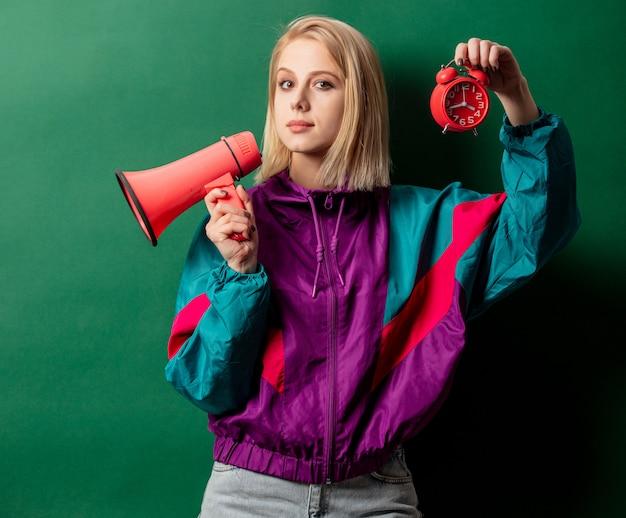 Mulher de casaco punk estilo anos 90 com alto-falante e despertador