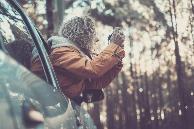 Mulher de casaco quente inclinado para fora da janela do carro, explorando e fotografando com a câmera dslr ao longo da floresta. mulher com cabelo encaracolado e casaco quente tirando fotos na floresta usando uma câmera digital