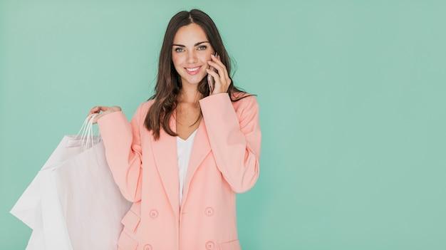 Mulher de casaco rosa com sacos de compras e smartphone