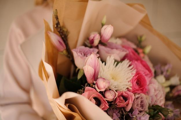 Mulher de casaco segurando um buquê de flores cor de rosa suave