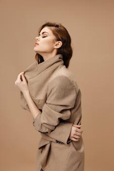 Mulher de casaco tocando gola com as mãos