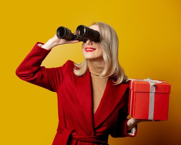 Mulher de casaco vermelho com binóculos e caixa de presente na parede amarela