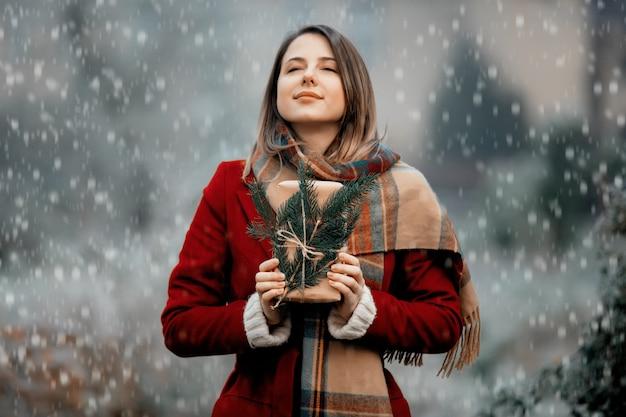 Mulher de casaco vermelho com caixa de presente no campo de neve