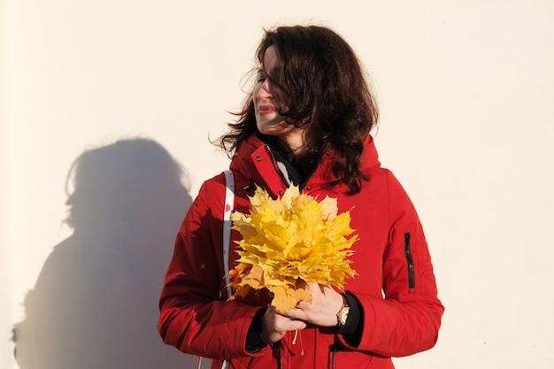 Mulher de casaco vermelho com folhas de bordo amarelas nas mãos