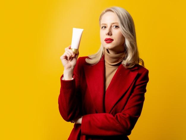 Mulher de casaco vermelho com tubo de creme na parede amarela