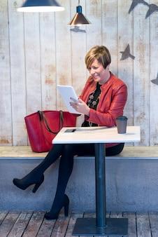 Mulher de casaco vermelho usando tablet em um café