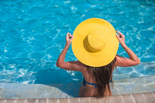 Mulher de chapéu amarelo relaxante na piscina
