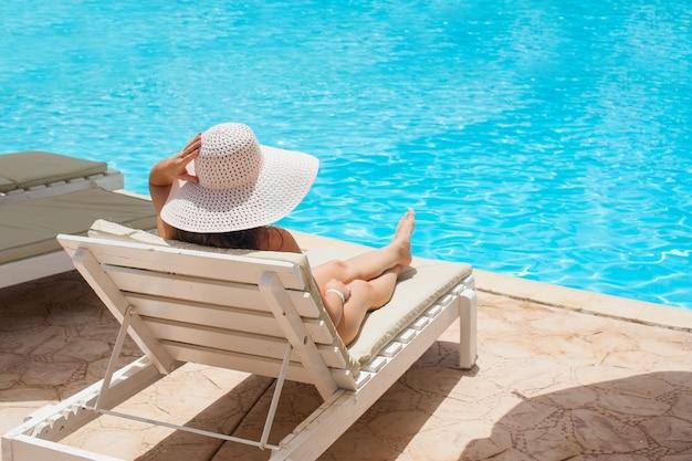 Mulher de chapéu branco deitada numa espreguiçadeira perto da piscina.