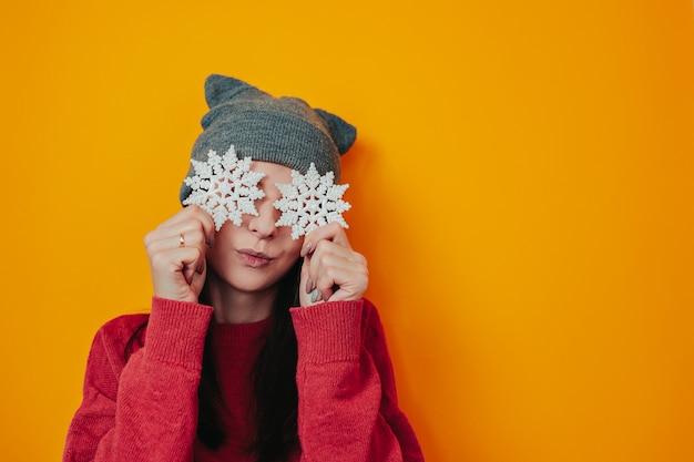 Mulher de chapéu cinza em fundo laranja. jovem de camisola e chapéu está segurando o floco de neve. cartão de natal com floco de neve.