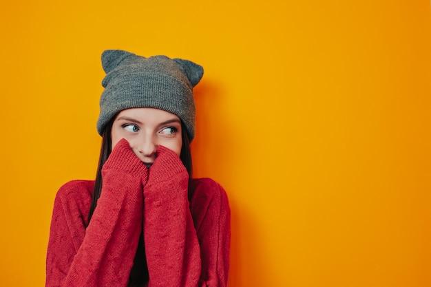 Mulher de chapéu cinza em fundo laranja. jovem de camisola e chapéu. o inverno está chegando. mulher está escondida na camisola.