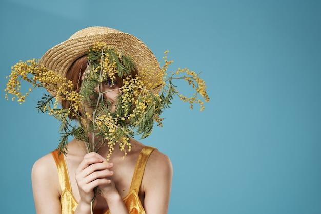 Mulher de chapéu com um buquê de flores feriado womens day charme fundo azul. foto de alta qualidade