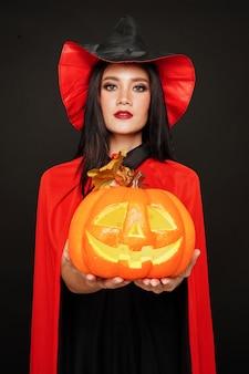Mulher de chapéu de bruxa e fantasia segurando abóbora no festival de halloween