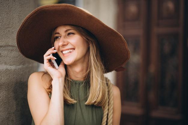 Mulher de chapéu de férias falando ao telefone