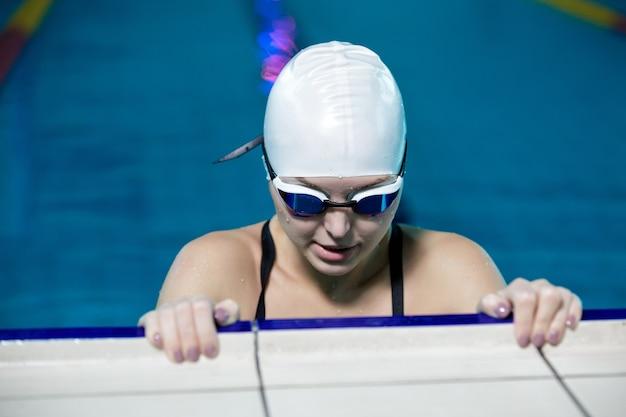 Mulher de chapéu de natação e óculos na piscina
