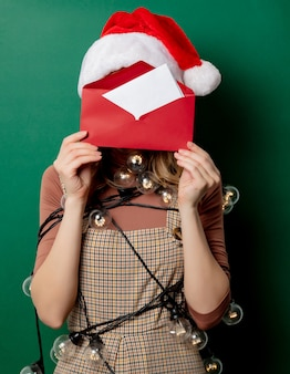 Mulher de chapéu de natal e correio em envelope