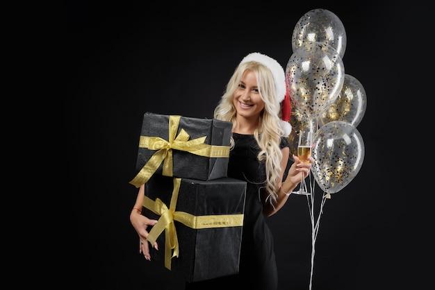 Mulher de chapéu de papai noel com caixas de presente na parede preta. balões dourados e férias de natal.