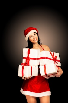 Mulher de chapéu de papai noel segurando presentes de natal sorrindo feliz e animada