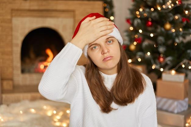 Mulher de chapéu de papai noel vermelho e suéter branco com forte dor de cabeça, com expressão facial triste, mantendo a mão na testa, sentada na sala rodeada de decoração de natal.