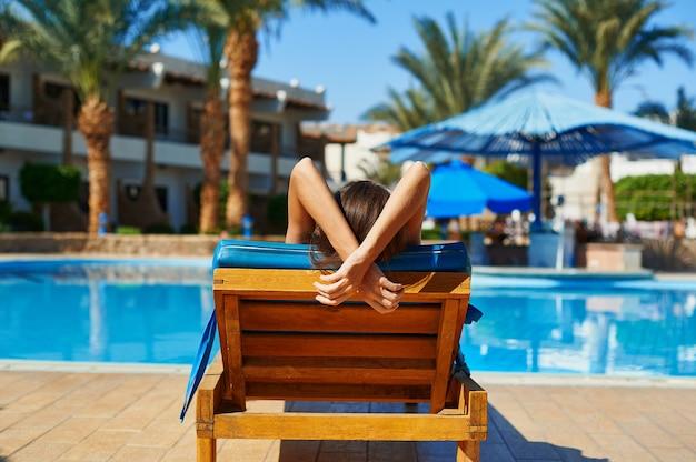 Mulher de chapéu deitada numa espreguiçadeira perto da piscina do hotel, conceito de verão para viajar.