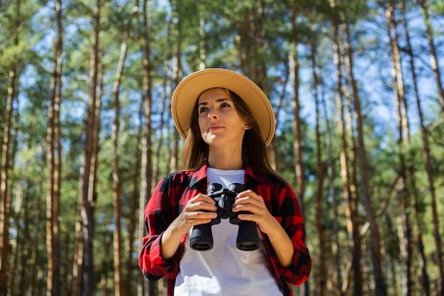 Mulher de chapéu e camisa xadrez vermelha segurando binóculos no fundo da floresta.