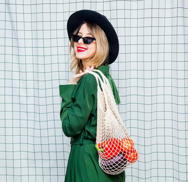 Mulher de chapéu e capa verde no estilo dos anos 90 com saco de rede