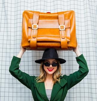 Mulher de chapéu e manto verde no estilo dos anos 90 com mala de viagem