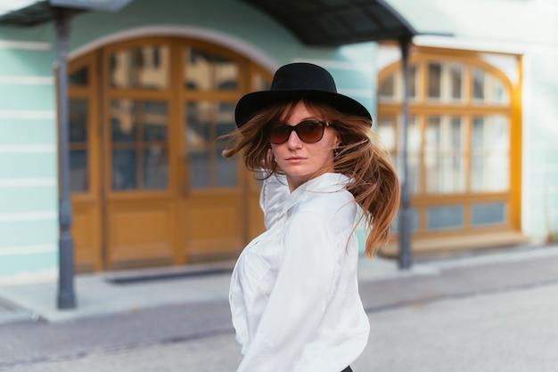 Mulher de chapéu e óculos escuros balançando os cabelos na cidade no verão