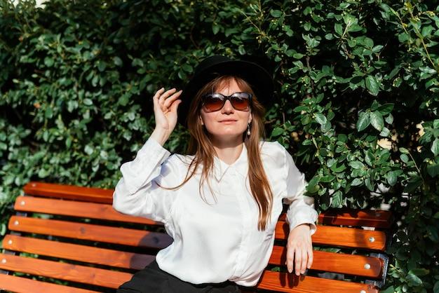 Mulher de chapéu e óculos escuros sentada em um banco e aproveitando o clima de verão