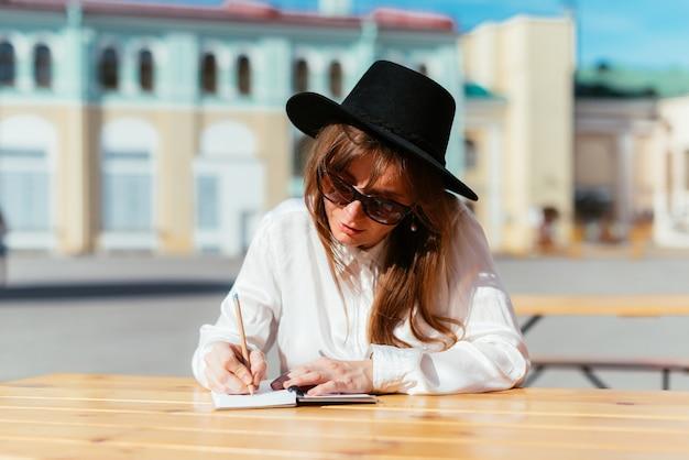 Mulher de chapéu e óculos escuros sorrindo enquanto está sentada em um café e fazendo anotações em um caderno
