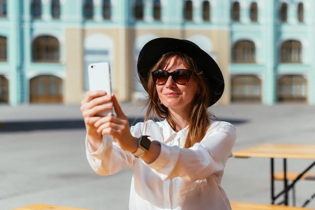 Mulher de chapéu e óculos escuros sorrindo enquanto está sentada em um café no verão e tira fotos em um smartphone