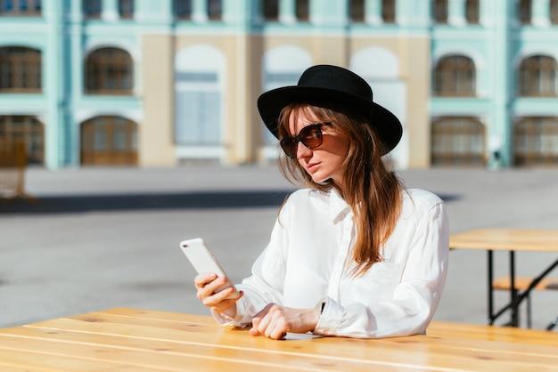 Mulher de chapéu e óculos escuros sorrindo enquanto está sentada em um café no verão e usa um smartphone