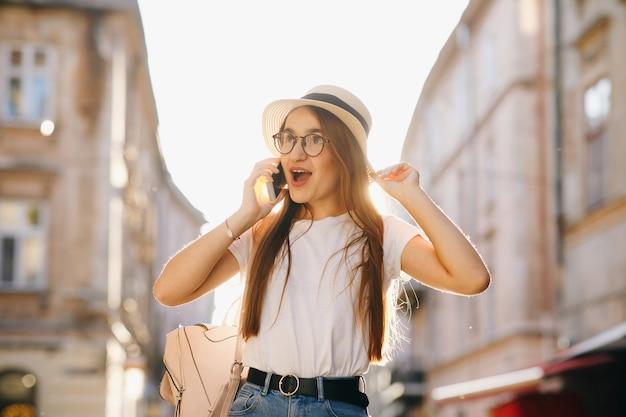 Mulher de chapéu e óculos fica na rua da cidade, falando no celular, sorrindo, rindo. menina hippie caminha. férias, aventura, viagem. dia de sol, luz de fundo.