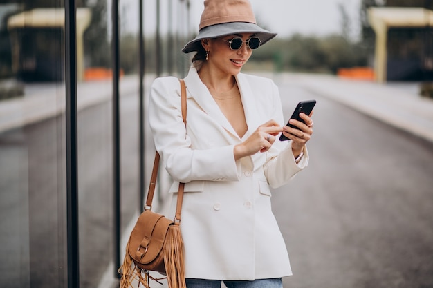 Mulher de chapéu e telefone fora da rua