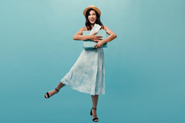 Mulher de chapéu e vestido feliz posa com mala azul e ingressos. menina alegre em um vestido de verão azul e sapatos pretos, posando em fundo isolado.