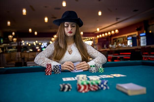Mulher de chapéu jogando cartas e fichas de pôquer no cassino