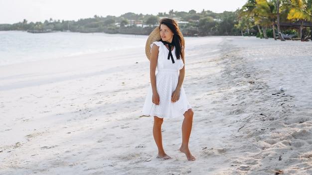 Mulher de chapéu na costa do oceano índico